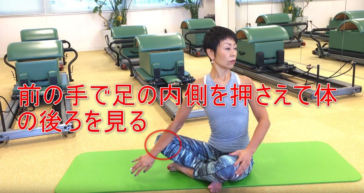 57-05_前の手で足の内側を押さえて体の後ろを見る
