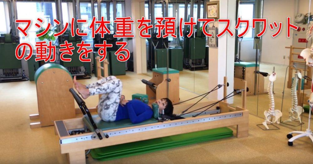 77-05_マシンに体重を預けてスクワットの動きをする